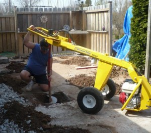 worker shown using ground hog post hole digger machine