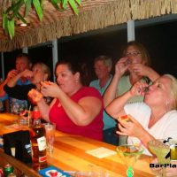 friends doing a shot at home tiki bar