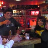 the website author pictured with friends around home bar