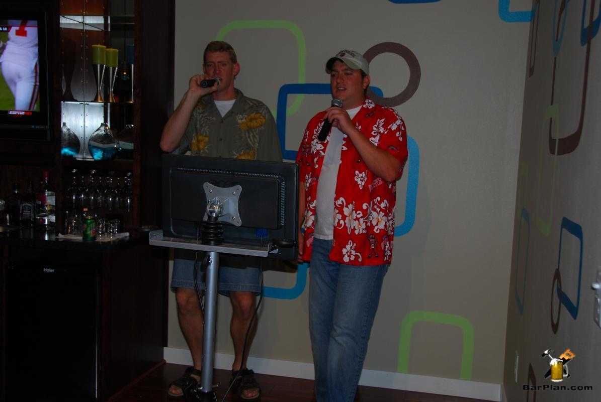 two men singing karaoke at home bar