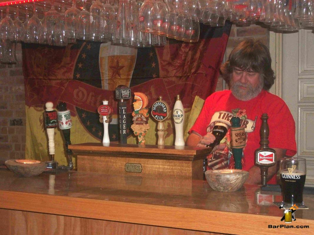 man pouring beer from home bar