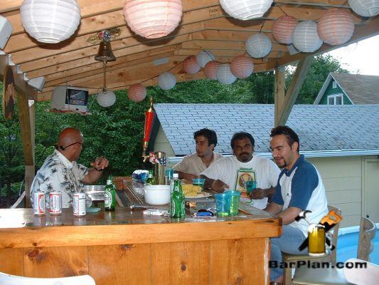 four people sitting around backyard tiki bar