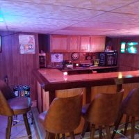 classic basement home bar with vintage hamms sign