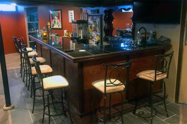 L-shaped basement home bar with stools
