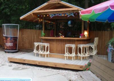 backyard tiki bar built on a deck with white bar stools